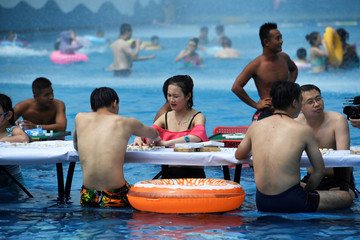People play Chinese chess and mahjong as they sit in water at a water park on a hot day in Chongqing