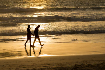 Silhouette of couple walking hand in hand and barefoot on golden beach and sea bokeh at sunset..Romantic time of life for a wonderful vacation in the island of dream..