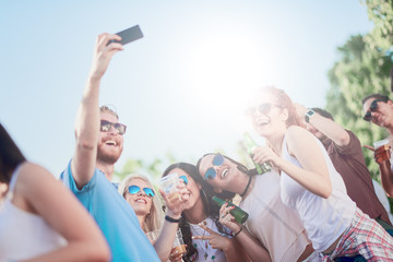 Friends taking selfie at outdoor party, sunlight at background
