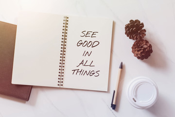 Inspirational motivating quote on notebook with pine cone, coffee cup and pen on white marble table background.