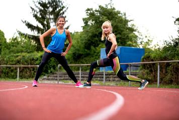 Freundinnen beim gemeinsamen Stretching auf einer Laufbahn