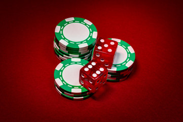 Casino craps and the gambling industry concept with closeup on a pair of dice sitting on green stacked chips with each die sitting on a different small stack, on red felt