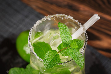 A glass filled with alcohol beverage from juicy lime, rum, fresh mint and crushed ice on a dark wooden background. Summer mojito with straw, top view.