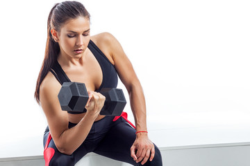 Young woman  with dark hair in a black sports top and elk sits and does an exercise on the biceps with a dumbbell in black on a white isolated background