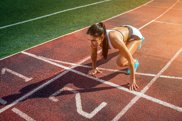 Young woman runner with dark hair in a white sports top and short shorts stands in a low start position before the start for a sprint race at the stadium on a summer day