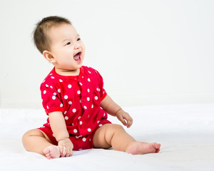Portrait of adorable infant baby girl sitting on the bed with copyspace