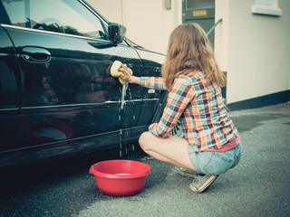 Young woman washing her car