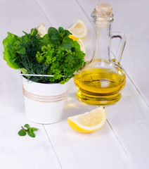 Fresh herbs in a bucket with lemon and olive oil