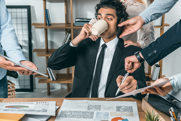 portrait of busy businessman drinking coffee and sitting at workplace while colleagues helping with work in office Wall mural