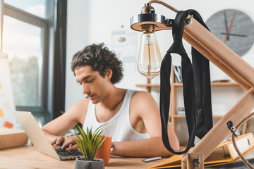 focused businessman in underwear typing on laptop at workplace in office