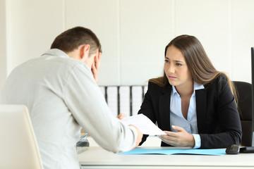 Sad boss firing an employee at office