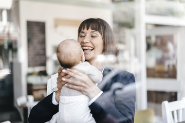 Businesswoman in cafe holding her baby