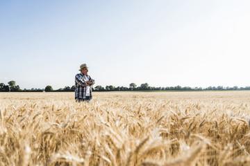 Happy senior farmer standing in wheat field Fotoväggar