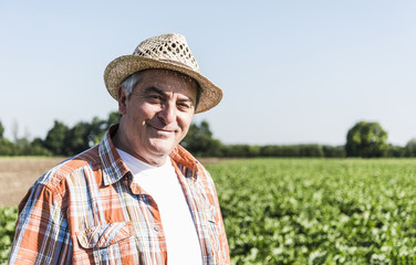 Portrait of content senior farmer standing in front of a field