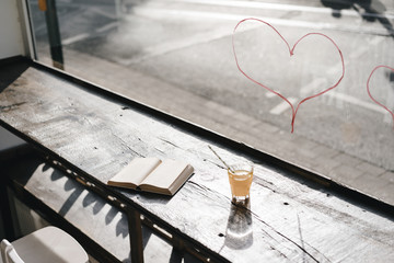 Book and drink on table in front of a window with lipstick hearts