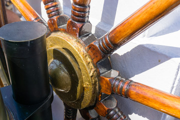 Steering wheel on the old ship. Nautical adventure of the ancient sailing vessel.