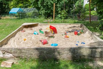 Großer Sandkasten mit Kinderspielzeug in einem Garten