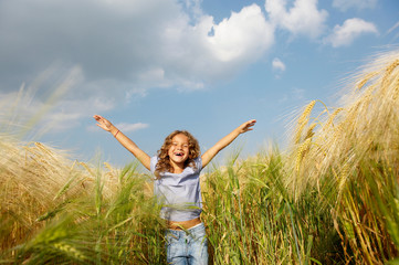 Girl playing in a wheat field