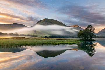 Photo sur Aluminium Lac / Etang A beautiful summer sunrise with early morning mists rolling through valley in the English Lake District.