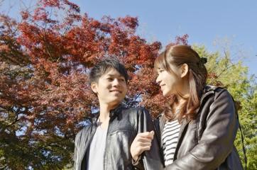 秋の公園でデートするカップル