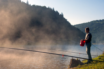Adult Man fishing early in the morning on mountain lake