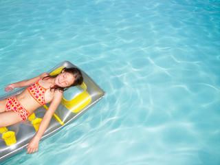 Girl on air mattress in pool