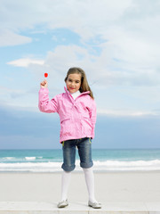 Young girl holding lollipop by sea