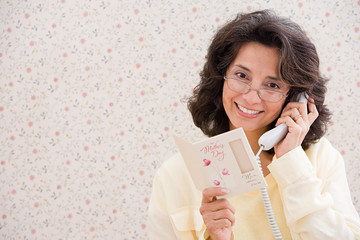 Woman on telephone with card