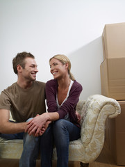 A couple sat on a sofa in their new home