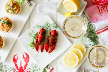Two red boiled crayfish with twig of dill on the white plate, wooden rustic table . Two snaps glass of liquor with salt on edge, white vine.