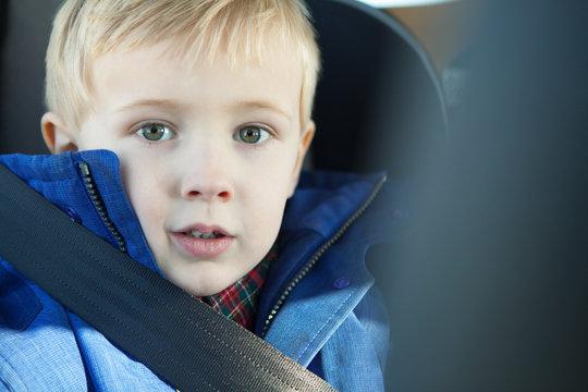 Young boy wearing car seatbelt