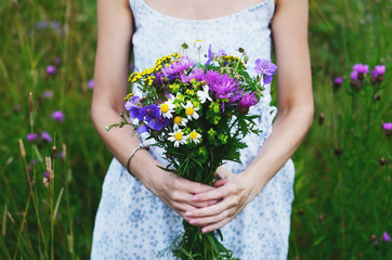 Woman in country style dress holding bouquet of colorful flowers in summer field