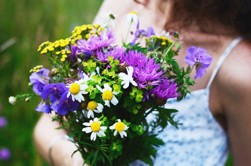 Girl with bouquet of colorful flowers in summer field
