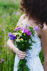 Dark haired woman in summer dress holding bunch of colorful flowers in her hand