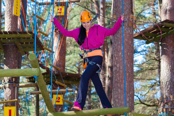 Cheerful attractive girl in a special outfit engaged in rock climbing.