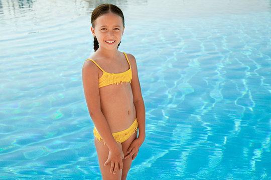 Girl in yellow bikini by swimming pool, portrait