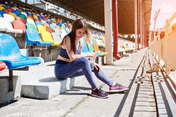 Gorgeous young fit woman sitting on a chair in the stadium.