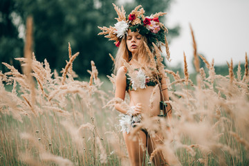 Beautiful little girl in image of nymph stands with closed eyes among grasses on meadow.