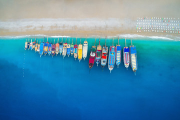 Photo sur Toile Vue aerienne Aerial view of colorful boats in mediterranean sea in Oludeniz, Turkey. Beautiful summer seascape with ships, clear azure water and sandy beach in sunny day. Top view of yachts from flying drone