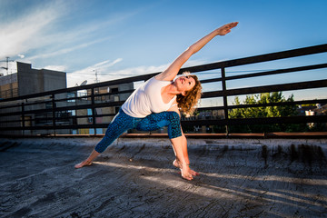 Fit mature woman doing yoga in sunset, urban landscape