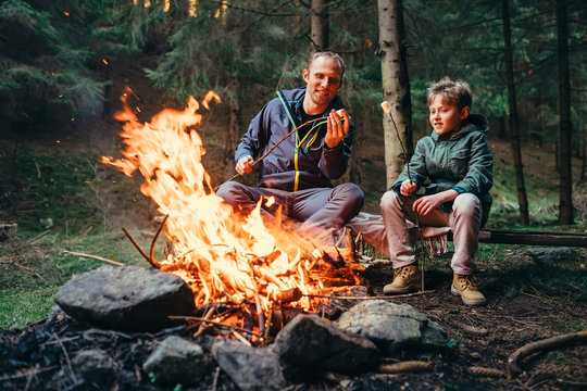 Father and son roast marshmallow on campfire