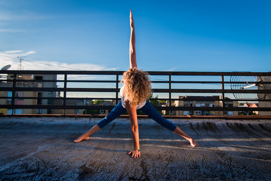 Urban yoga - power pose with a waist twist, physically fit mature woman practicing yoga on a rooftop