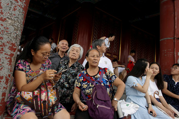 People look at the Forbidden City from a hilltop in Jingshan Park in Beijing
