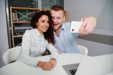 Smiling business people taking selfie smartphone while sitting deskoffice