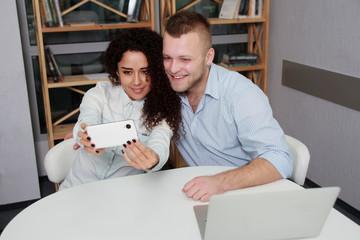 Smiling business people taking selfie smartphone while sitting deskoffice