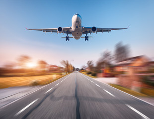 Poster Avion à Moteur Passenger airplane with motion blur effect. Airplane is flying in the sunset sky over the rural asphalt road at sunset in Netherlands. Landing airplane with blurred background. Aircraft. Business trip