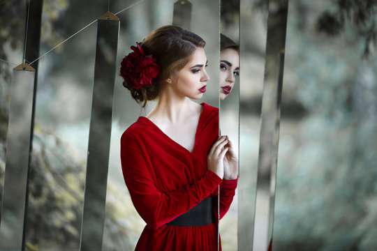 Mysterious girl in a long red dress watch mirrors in the nature.