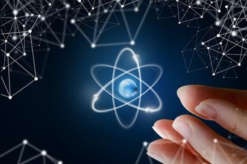 Female hand show the atom .