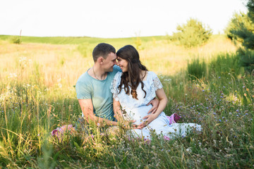 Romantic kissing Pregnant couple in a wheat field. Pregnant woman with her husband holding big belly with baby inside in nature on a beautiful sunny day