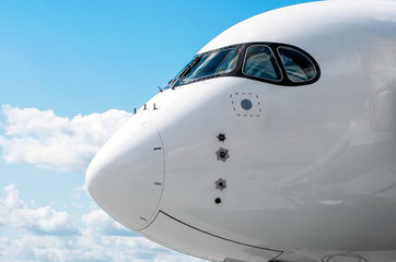 Passenger airplane nose cockpit in blue clouds sky